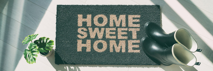 Autumn rain boots at home door entrance home sweet home mat banner. Panoramic background of shoes left at house doormat.