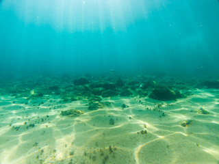 View of the seabed with sun rays reflected in the sand