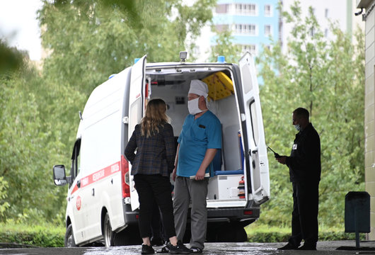 A woman talks to a medical worker outside a hospital where Russian opposition leader Navalny was admitted, in Omsk