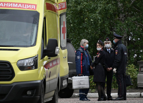 A medical worker speaks to police officers outside a hospital where Russian opposition leader Navalny was admitted, in Omsk