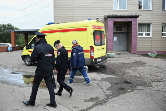 A medical worker and police officers walk outside a hospital where Russian opposition leader Navalny was admitted, in Omsk