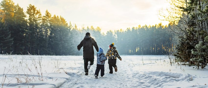Father and two children in winter forest