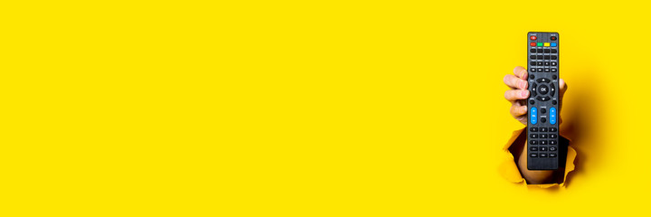 Female hand holding a TV remote control on a bright yellow background. Banner.