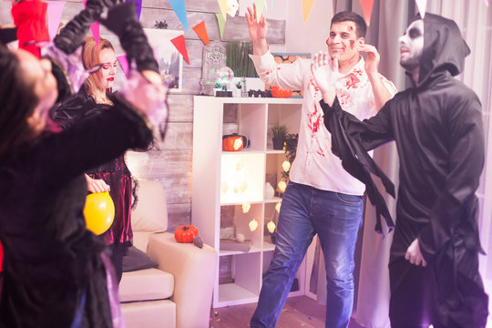 Spooky zombie smiling while dancing at halloween party with group of people.