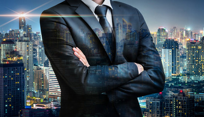 Double exposure of business man folded arms on city night background for successful of investment