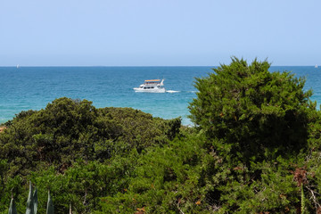 Boat passing in front of the sand dunes that give access to La Barrosa beach in Sancti Petri, Cádiz, Spain.