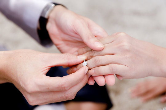 Closeup hands of groom and bride in wearing wedding ring ceremony. Diamond ring for engagement