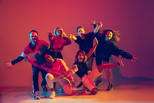 Young and crazy. Stylish men and woman dancing hip-hop in bright clothes on green background at dance hall in neon light. Youth culture, movement, style and fashion, action. Fashionable portrait.