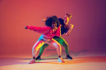 Photo Blinds Dance School Drive in motion. Stylish man and woman dancing hip-hop in bright clothes on green background at dance hall in neon light. Youth culture, movement, style and fashion, action. Fashionable portrait.