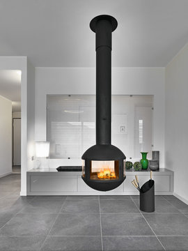 modern living room interior in the foreground  the  iron fireplace suspended from to ceiling