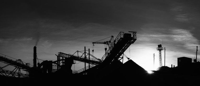 Black-white panorama of stone crushing equipment on the mining factory, silhouettes of constructions illuminated by sunset light against a black sky.