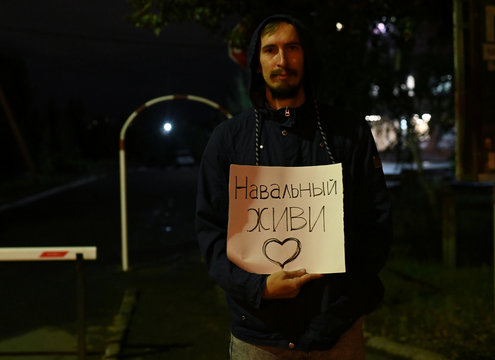 A man holds a placard outside a hospital where Russian opposition leader Alexei Navalny was admitted, in Omsk