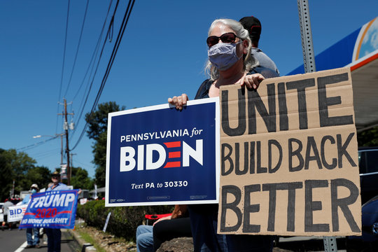A woman holds a sign in support of Democratic presidential nominee Joe Biden as supporters of U.S. President Donald Trump gather ahead of his campaign stop in Old Forge
