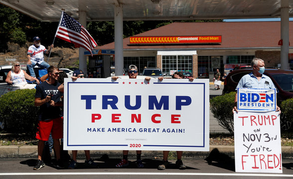 A man holds a sign in support of Democratic presidential nominee Joe Biden as supporters of U.S. President Donald Trump gather ahead of his campaign stop in Old Forge