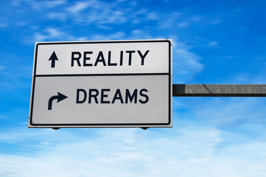 Reality versus dreams. Road sign with words reality and dreams. White two street signs with arrow on metal pole. Directional road. Crossroads Road Sign, Two Arrow. Blue sky background.