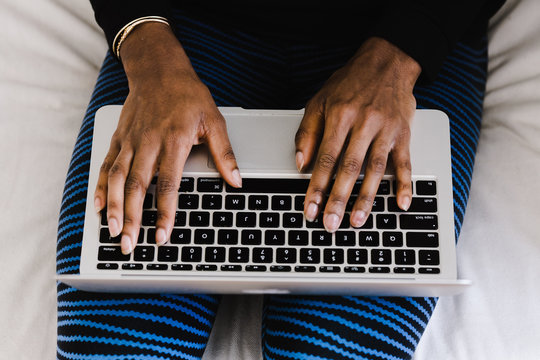 Overhead view of woman's hands on laptop keyboard