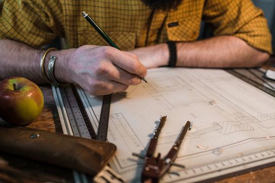 Die Hand eines bärtigen Mannes in Hemd zeichnet eine technische Zeichnung auf einem Zeichenbrett