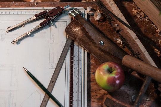 Verschiedene Zeichen-Utensilien, wie Zirkel, Lineal, Bleistift und Leder-Etui, liegen auf einer technischen Zeichnung