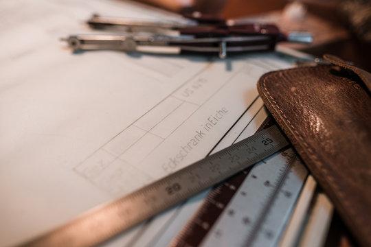Technische Zeichnung umgeben von Zeichen-Utensilien, wie Zirkel, Stahl-Lineal und Leder-Etui
