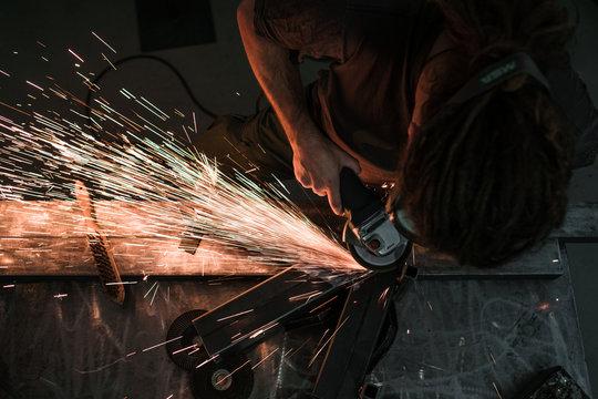 Mann mit Schutzbrille schleift mit einem Winkelschleifer unter Funkenflug eine Stahlkonstruktion
