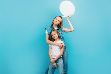 girl in white t-shirt and jeans looking at camera while mother holding thought bubble isolated on blue