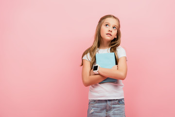 thoughtful child in smartwatch looking away while holding book isolated on pink