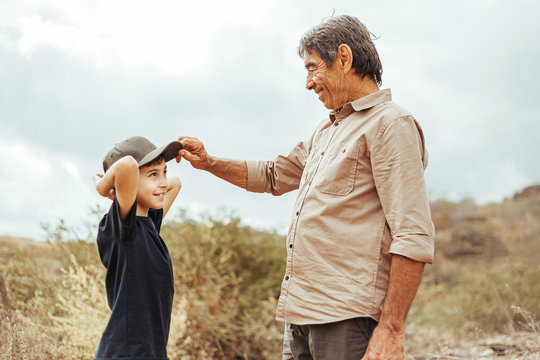 Latin grandfather and grandson in outdoor activities. Grandfather wears his cap on his grandson