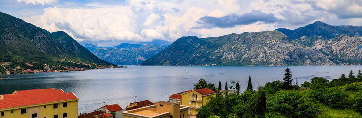 Aerial scenic view of residential buildings along the coast of Kotor Bay and mountains in the background in the summer in Dobrota, Montenegro