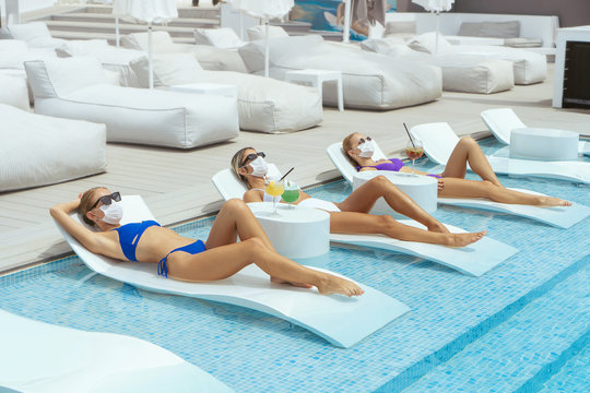 People with face mask rest in resort beach and keeping social distance in pool, after pandemic covid-19, summer vacation concept.