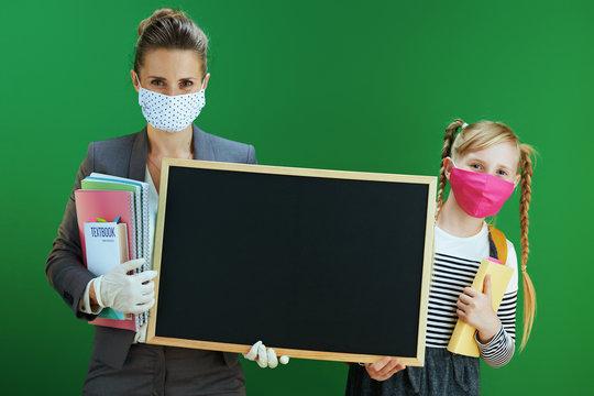 modern teacher woman and school girl showing blank board