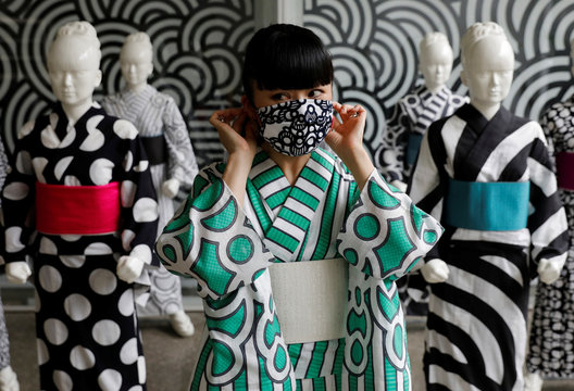 Japanese artist Hiroko Takahashi wears a protective face mask to pose for a photograph in front of mannequins displaying yukata, a lighter kimono which she designed, at her studio in Tokyo