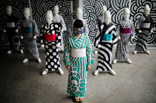 Japanese artist Hiroko Takahashi wears a protective face mask as she poses for a photograph in front of mannequins displaying yukata, a lighter kimono which she designed, at her studio in Tokyo