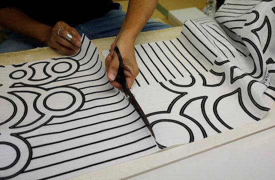 Kimono tailor Kazumi Furuoya works on a fabric Japanese artist Hiroko Takahashi designed, at his studio in Tokyo