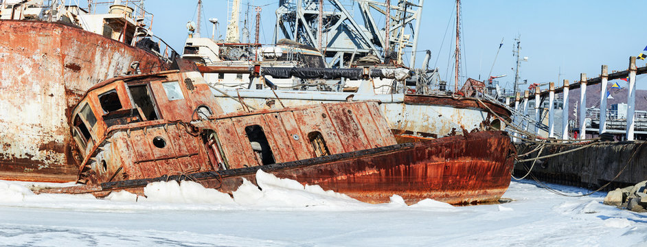 Abandoned rusty ship without people in the ice. Photo of a lone commercial vessel at the cemetery of ships in Russia, Primorsky Krai. Rusty ship concept for travel site