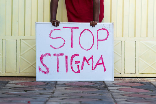 "Black person holding a sign with text ""Stop Stigma"""