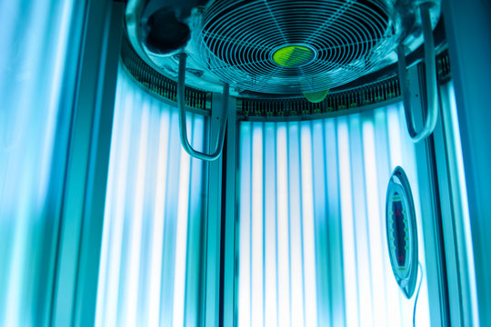 Vertical Tanning turbo Solarium Light Machine with glowing blue light ultraviolet lamps for tanning and skin care. Empty tanning Modern  solarium, inside. Open Solarium door. Control panel on the side