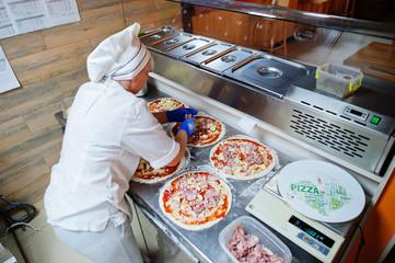 Female chef preparing pizza in restaurant kitchen. Wall mural