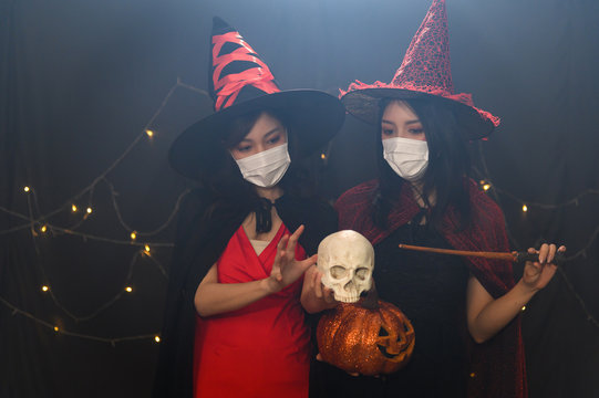 Portrait of two beautiful young woman in witch halloween costumes wearing protection face mask against coronavirus in halloween party