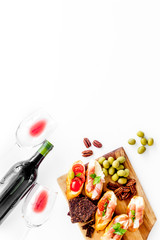 Fototapete - Wine appetizer. Toasts, nuts, olives on white desk top view copy space
