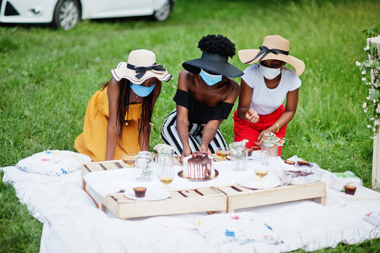 Group of african american girls with facial masks celebrating birthday party outdoor with decor during coronavirus pandemia.