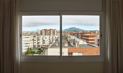 City with a mountain in the background seen through a large window with curtains on the sides