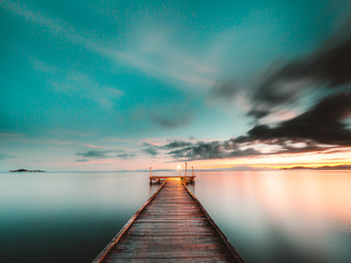 Wooden jetty at sunset over the ocean, long exposure
