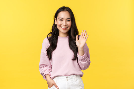 Lifestyle, emotions and advertisement concept. Cute stylish asian girlfriend waving hand to say hi, smiling friendly as greeting someone, make hello or welcome gesture, yellow background