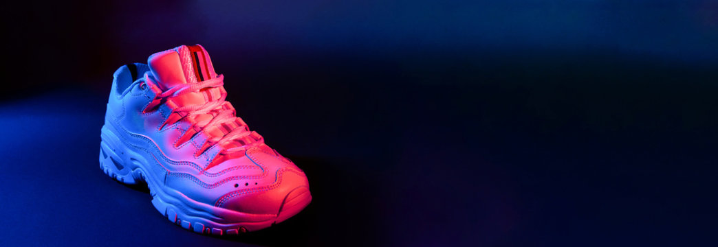 White sneaker on black background in the neon red and blue light. Banner.