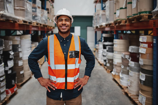 Portrait of successful manager standing in warehouse between shelf filled with goods wearing a white helmet and orange vest for protection with hands on waist