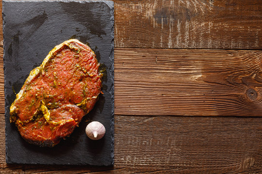 slice of raw meat on slate slab with garlic on wooden table