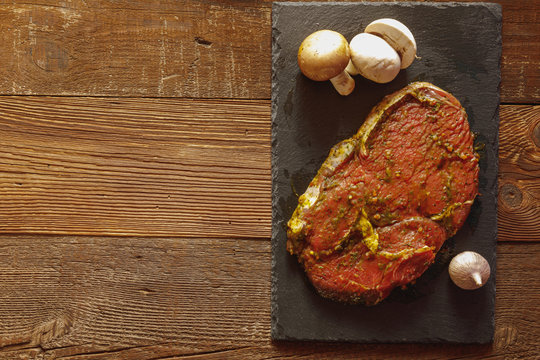 Slice of spiced raw beef on slate plate with garlic and mushroom on wooden table