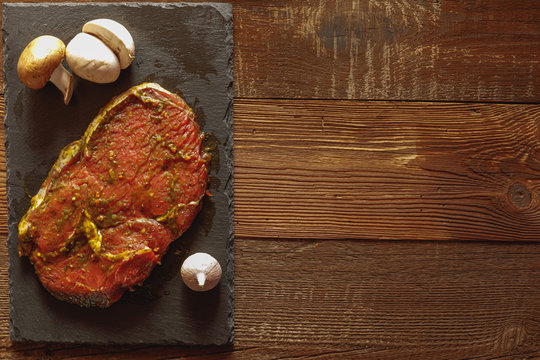 Slice of raw beef on slate plate with garlic and mushroom on wooden table