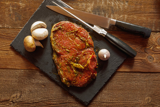 Slice of spiced raw beef with garlic and mushroom on slate plate with meat knife and fork on wooden table