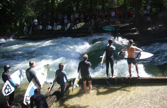 People watch as a surfer catches a wave in the freezing water of the Eisbach River in the Munich's famous English Garden, in Munich